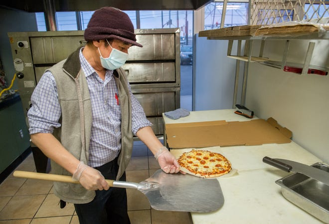 Sam Mach lays out a freshly-baked pizza from the oven at his new pizzeria George's Pizza,  234 Camp St. in East Peoria. Mach, an entrepreneur and restaurateur who owns the Village Square shopping center where his restaurant is located, named the new business after his old boss and friend Fred George who gave Mach his start decades ago.