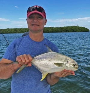Brian King of St. Simons, Georgia shows off a keeper size pompano he caught in lower Tampa Bay while fishing with Capt. Rick Gross of Bradenton this week.