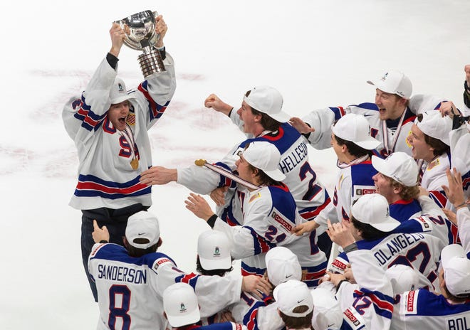United States' Cam York (4) hoists the trophy after the team's win over Canada in the title game in the IIHF World Junior Hockey Championship, Tuesday, Jan. 5, 2021, in Edmonton, Alberta.