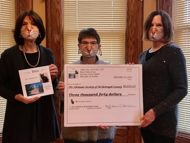 """Authors Brenda Sayre and Patti Nemec were happy to present Bonnie Smith-Skripps (President of the Humane Society of McDonough County) with a check for $3,040.00 in donations received in support of their book, """"Binx the Uptown Cat"""". The book tells the true story of Binx's rescue from life as a homeless cat living on the Macomb square into a cozy home with a loving family of his own. The book was available this fall for a donation of $25.00. All donations received for the book (and additional gifts included) were given to the Humane Society of McDonough in hopes of helping their dream of a new animal shelter in McDonough County come true. The response was amazing. Brenda and Patti extend their most sincere """"thanks"""" to everyone who generously supported this project. There are no more books available at this time. Keep your eye out for a possible 2nd printing in Spring 2021."""