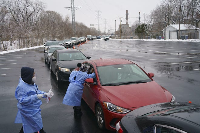 Cars line up as Tamira Perkins, center, and Kiara Flowers administer a COVID-19 test at a walk-up and drive-thru test site in the Evanston Township High School parking lot in Evanston on Jan. 3, 2021.