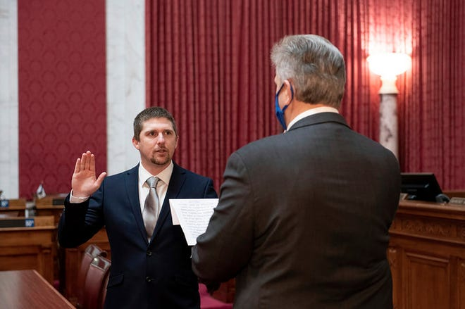W. Va. Del. Derrick Evans, shown taking the oath of office in Charleston on Dec. 14, 2020 was seen in a video as part of the group of pro-Trump rioters who forced their way into the U.S. Capitol on Wednesday.