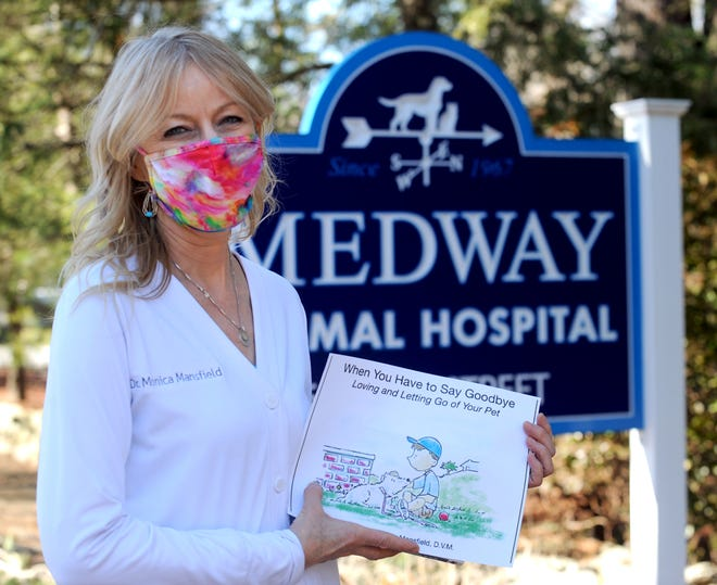 "Dr. Monica Mansfield  is seen with one of her two books at the Medway Animal Hospital on Jan. 7, 2021. She was inspired by the James Herriot books, which are the basis for the PBS Masterpiece series ""All Creatures Great and Small."""
