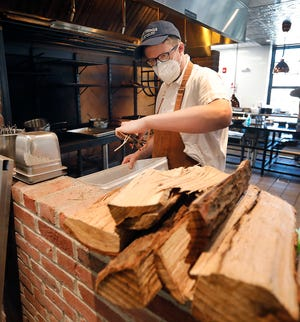 Co-owner and chef Marc Sheehan, of Quincy, at work in front of his wood-fired stove at the Northern Spy restaurant in Canton on Thursday Jan. 7, 2021.