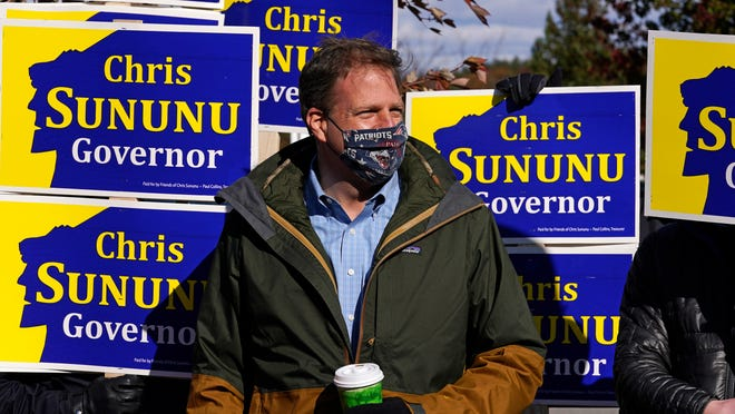 N.H. Gov. Chris Sununu stands with supporters at a polling station at Windham, N.H. High School, Tuesday, Nov. 3, 2020, in Windham.