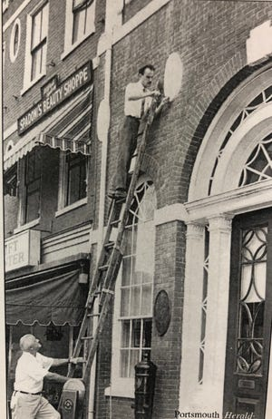 In this Portsmouth Herald photo, Garland Patch Sr. holds the ladder in September 1968 as James Garvin remounts a newly restored oval patera on the facade of the Portsmouth Athenaeum in Market Square.