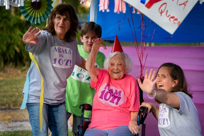 Grace Glorius celebrates her 107th birthday with family members Sharon Ghioto (left), Griggs Justiss, 10, and Lauren Justiss during a drive-by parade in her honor in suburban West Palm Beach on Wednesday.
