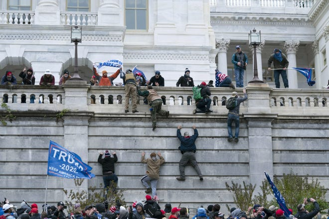 Supporters of President Donald Trump climb the west wall of the U.S. Capitol on Wednesday.
