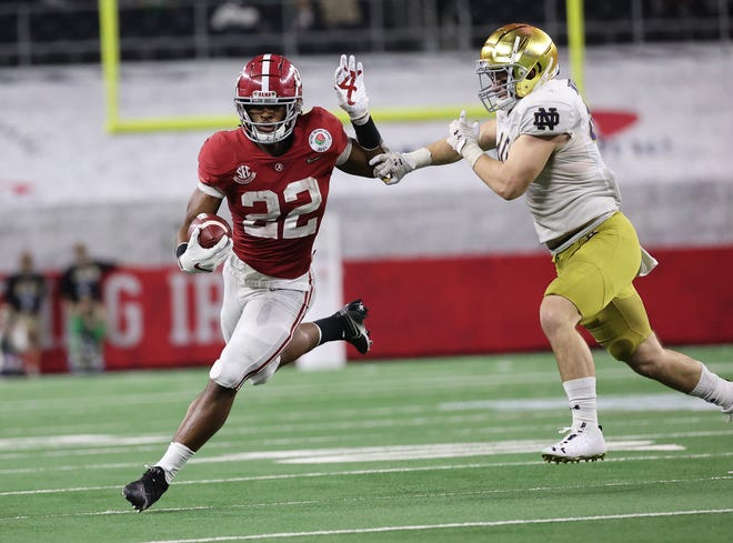 Najee Harris runs around Notre Dame linebacker Drew White during Alabama's victory over the Fighting Irish in the college football playoffs semifinal last Friday,