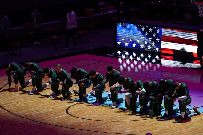 Jan 6, 202 1; Miami, Florida, USA; Boston Celtics players kneel during the playing of the national anthem prior to the game against the Miami Heat at American Airlines Arena. Mandatory Credit: Jasen Vinlove-USA TODAY Sports