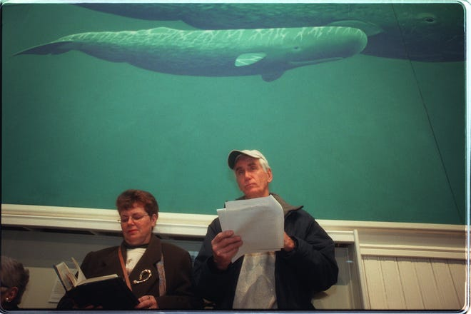 Maura Saltmarsh and her husband Bob Saltmarsh follow along in the reading of Moby Dick in 1999 under a whale painting at the musem.
