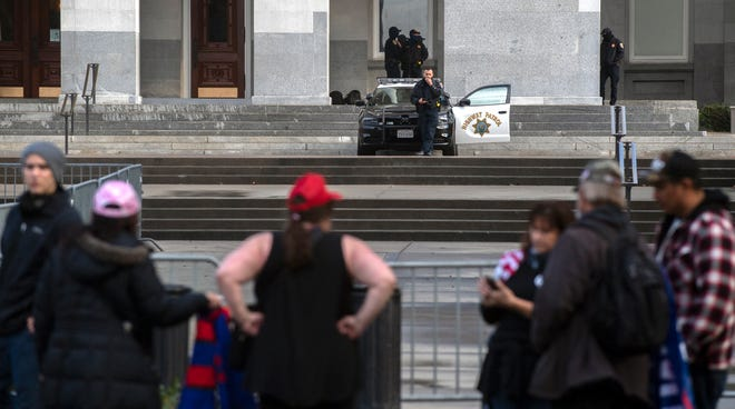 California Highway Patrol officers continue to guard the west entrance to the California State Capitol building after the end of a rally of Trump supporters over the 2020 election results.