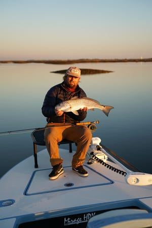 Captain Cullen Traverso with a redfish caught in the flats on fly tackle. The shallow water and dark bottoms of the flats are several degrees warmer than the ICW itself and redfish are schooling up in big schools in the backwaters, taking advantage of the warmer water.