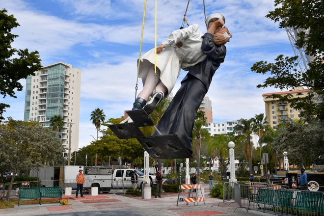 """The """"Unconditional Surrender"""" statue is lowered onto its new location at Bayfront Park on Thursday. The statue was moved to make room for a diversion road while the Florida Department of Transportation begins construction of a traffic roundabout at Gulfstream Avenue and U.S. 41."""