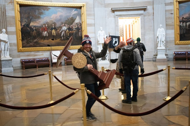 A pro-Trump protester, who has been identified as Adam Johnson of Parrish, carries the lectern of U.S. Speaker of the House Nancy Pelosi through the Rotunda of the U.S. Capitol Building after a pro-Trump mob stormed the building on Wednesday.