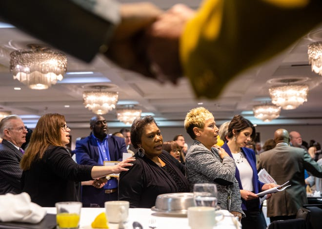 """Rita Roach, center, and Kristin Doster, right, join hands as they sing """"We Shall Overcome"""" during the annual Springfield Frontiers International Club Dr. Martin Luther King Jr. Memorial Breakfast at the Wyndham Springfield City Centre, Monday, Jan. 20, 2020, in Springfield, Ill. [Justin L. Fowler/The State Journal-Register]"""