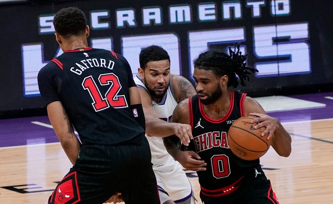 Sacramento Kings guard Cory Joseph, center, tries to fight past the screen set by Chicago Bulls forward Daniel Gafford, left, as he pursues Coby White in Sacramento, Calif., Wednesday. The Kings won 128-124.