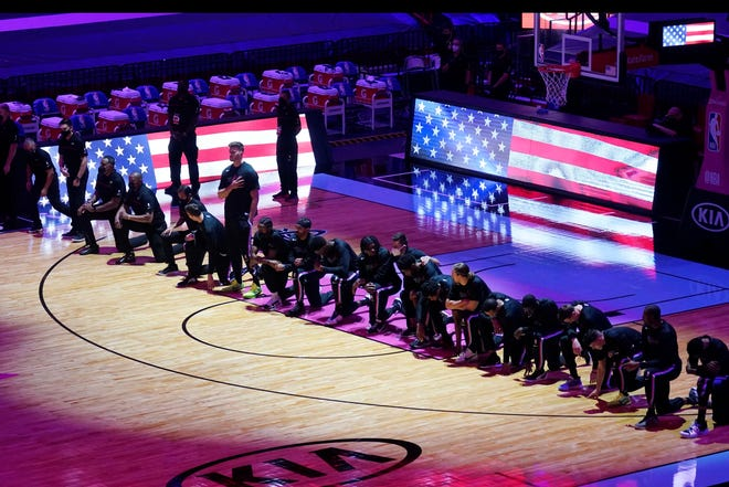 The Boston Celtics team kneels during the playing of the National Anthem before the first half of an NBA basketball game against the Miami Heat, Wednesday, Jan. 6, 2021, in Miami.