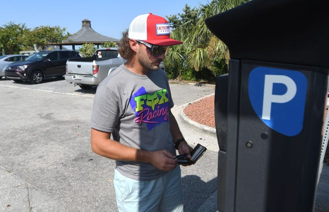 Kyle Fox pays for parking at the Wynn Plaza parking lot in Wrightsville Beach, N.C., Tuesday, July 28, 2020. Kure Beach, the only town in New Hanover County that offers free parking, may be moving to a paid parking system soon.