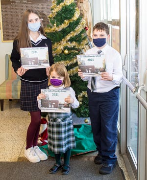 Our Lady of Lourdes School students Erin Watts, eighthgrade, Reagan Lawrence, first grade, and Jonathan Kotlikoff, fourth grade, are asking for supporters to purchase anOLOL School Calendar. (Photo by John Gouveia)