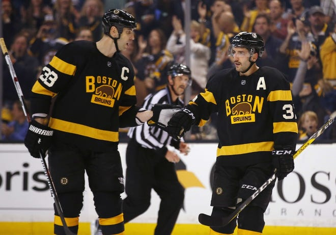 The Bruins' Patrice Bergeron, right, will trade in his 'A' and now will wear the 'C' previously worn by Zdeno Chara, left.
