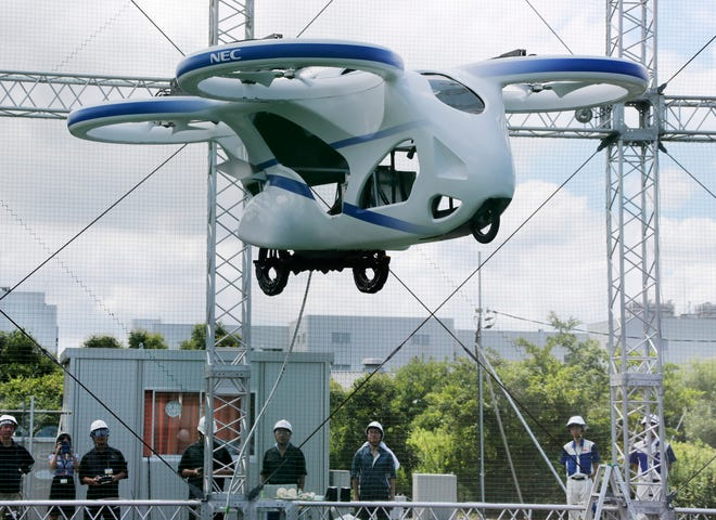 """Japanese electronics maker NEC Corp. demonstrates its """"flying car,"""" a large drone-like machine with four propellers."""
