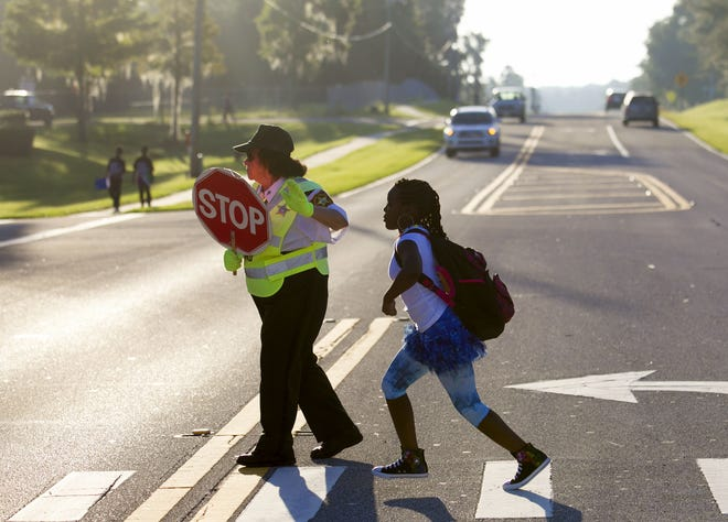 A crossing guard helps a student at a crosswalk.