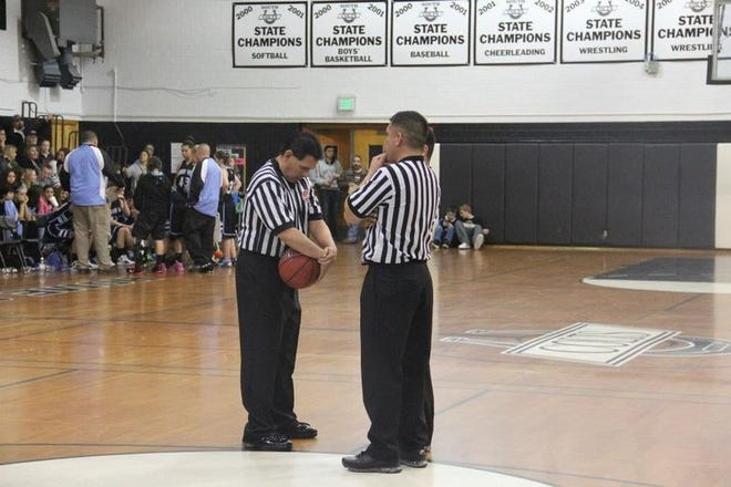 Pueblo basketball officials Jerry Santos, left, and Ted Garcia discuss strategy during a game at  Jerry Kersey Gym at Pueblo West.