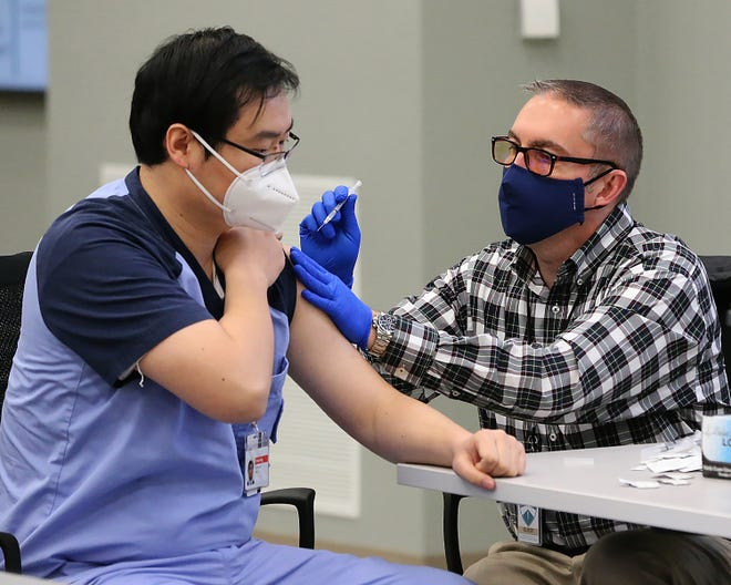 Arkansas College of Osteopathic Medicine (ARCOM)  fourth year medical student He Zhexiang receives a COVID-19 vaccine shot from Health Depot Pharmacist John Hall, Wednesday, Jan. 6, at the Chaffee Crossing campus. More than 50 third and fourth year medical students received the first of two shots due to their clinical rotations in facilities actively seeing patients.