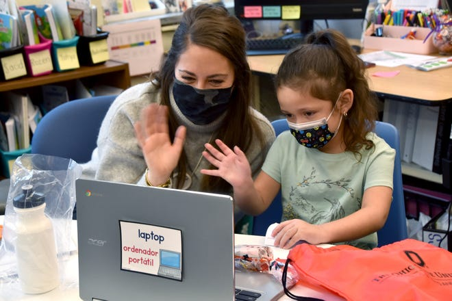 Longfellow Elementary School English teacher Kristin W. Potter and kindergarten student Bridget Moreno Serrano wave at their Bilingual Storybook Project partners at the Ohio State University during a Google Meet on Dec. 14.