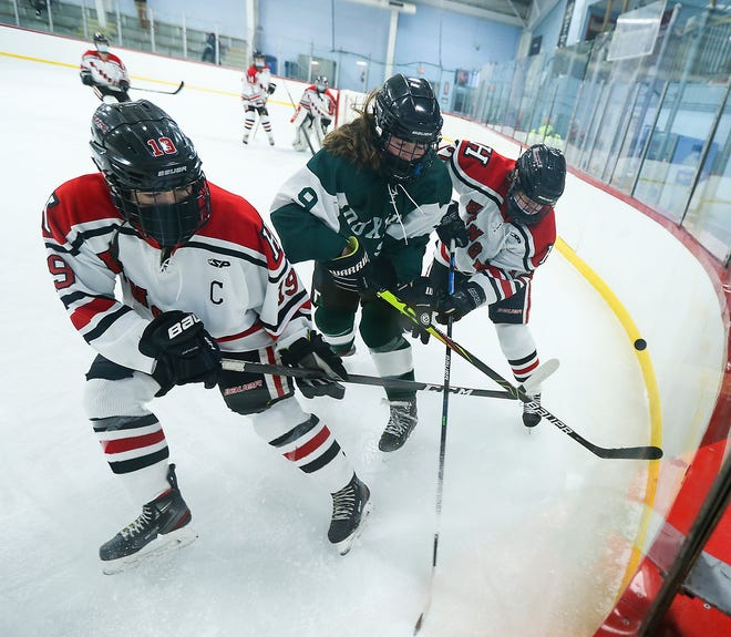 Hingham's Kathryn Karo and Hingham's Natasha Neelon battle Duxbury's Ayla Abban along the boards for the puck during first period action of their game at Pilgrim Arena on Wednesday, Jan. 6, 2021.