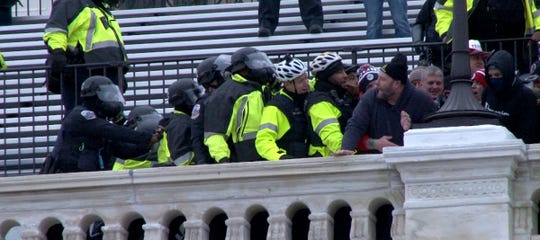 Police push a man off the Capitol steps after a pro-Trump mob took over the steps of the building in Washington, DC, Wednesday, January 6, 2021