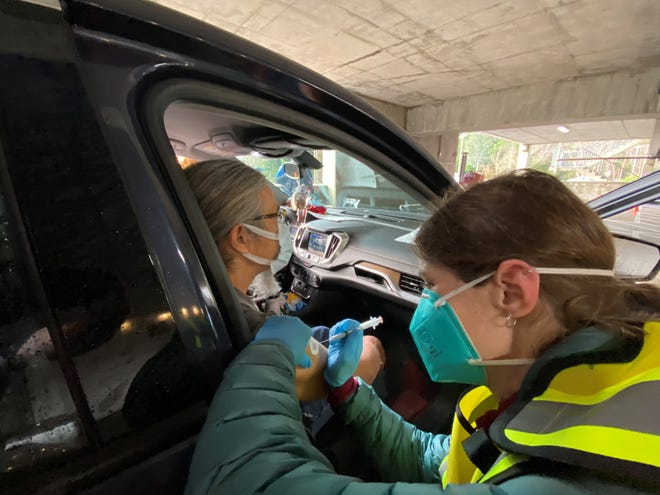 Lisa Pratt, an advanced registered nurse practitioner with the Suquamish Tribe, administers a shot to a tribal elder during a drive-thru clinic at Port Madison Indian Reservation on Tuesday.