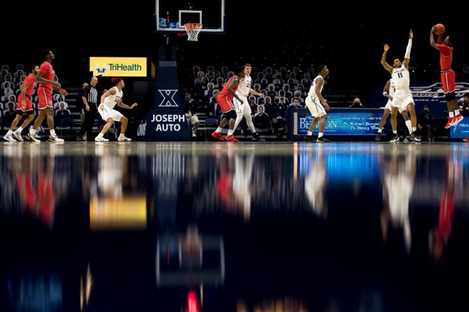 St. John's Red Storm guard Rasheem Dunn (3) hits a 3-pointer over Xavier Musketeers guard Dwon Odom (11) in the first half of the NCAA men's basketball game between the Xavier Musketeers and the St. John's Red Stormon Wednesday, Jan. 6, 2021 at Xavier University in Cincinnati.