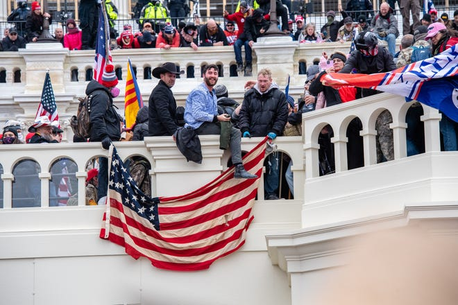 People sit atop railings outside the windows of the U.S. Capitol building.