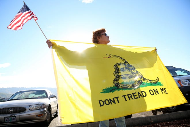Leslie Corp holds up an American flag and the Gadsden flag while waiting outside of Roseburg Municipal Airport for President Barack Obama's arrival in Roseburg, Oregon, on Friday, Oct. 9, 2015. Gun-rights activists say they planned to protest potential gun restrictions when Obama visited. (AP Photo/Ryan Kang)