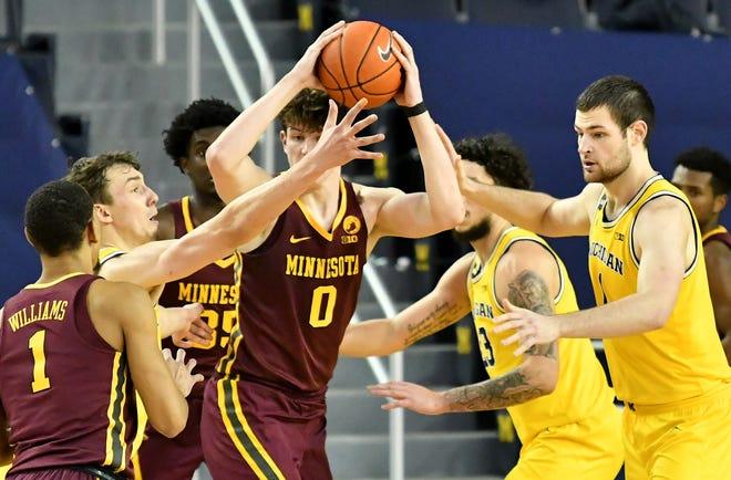 Michigan menahan center Minnesota Liam Robbins (0) dengan lima poin dalam kemenangan besar Rabu.
