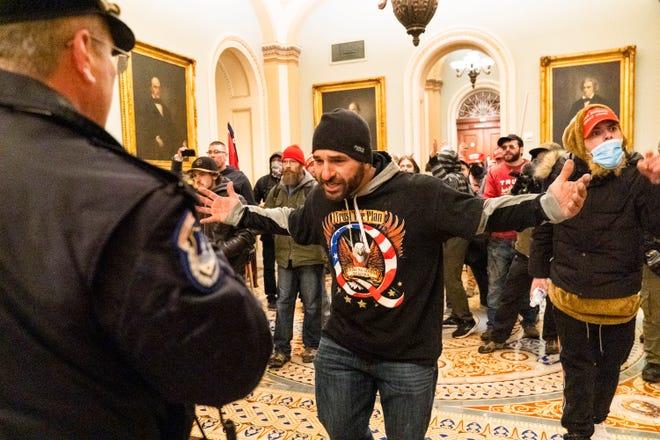 Pendukung Presiden Donald Trump dihadapkan oleh petugas Kepolisian Capitol di luar Kamar Senat di Capitol, Rabu, 6 Januari 2021 di Washington.