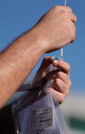 An oral swab is placed in its container as part of the COVID-19 testing procedure.