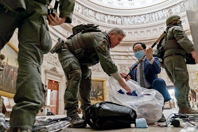 Le représentant Andy Kim, DN.J., aide les policiers de l'ATF à nettoyer les débris et les effets personnels éparpillés sur le sol de la rotonde aux petites heures du matin du jeudi 7 janvier 2021, après que les manifestants ont pris d'assaut le Capitole à Washington, le Mercredi.