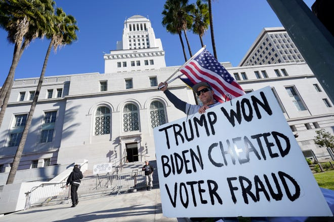 A protester holds a sign outside of City Hall Wednesday, Jan. 6, 2021, in Los Angeles. Demonstrators, supporting President Donald Trump, are gathering in various parts of Southern California as Congress debates to affirm President-elect Joe Biden's electoral victory. (AP Photo/Marcio Jose Sanchez)
