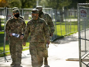 Arizona Army National Guard troops walk inside the secure fencing perimeter at the Arizona state Capitol in Phoenix on Jan. 7, 2021. No troops will be sent to Washington for the presidential inauguration.