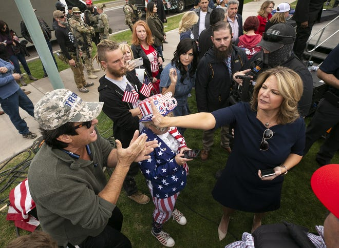 Arizona Republican Party Chair Kelli Ward puts her hand in the face of a man who was yelling at her for signing off on a certificate of accuracy for Maricopa County voting machines, after Ward spoke onstage during a pro-Trump rally at the state Capitol in Phoenix, on the day that the U.S. Congress was meeting in Washington, D.C., to certify the results of the presidential election, on Jan. 6, 2021. Pro-Trump supporters rampaged at the U.S. Capitol building later that day.