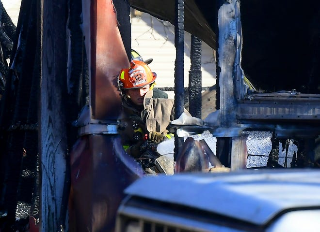 A firefighter douses hot spots at a mobile home fire in Jackson Township Thursday, Jan. 7, 2021. Bill Kalina photo