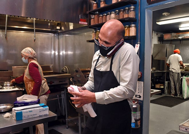 Serj Johal, owner of Thali restaurant in downtown Reno, takes an order over phone on Jan. 6, 2021. Reno area restaurants are struggling amid the pandemic.