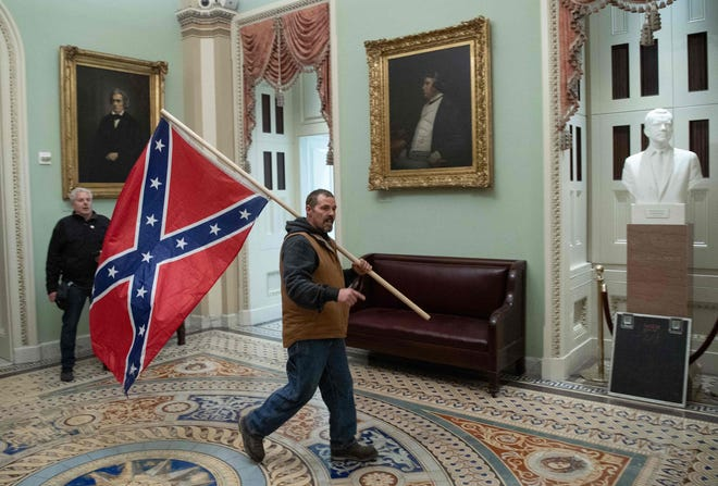 A Pro-Trump rioter carries a Confederate flag near the US Capitol Rotunda on Jan. 6, 2021, in Washington, DC.