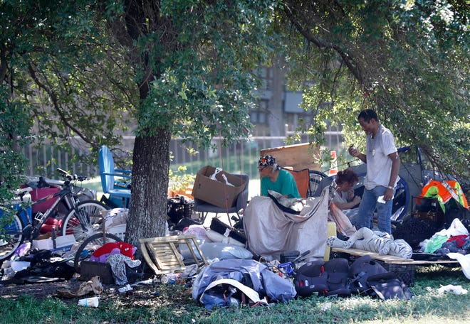 A woman and two men sit and talk along Riverside Drive at a homeless camp on Tuesday, May 19, 2020.  The unsheltered homeless population increasing by 45% in the Austin Area.