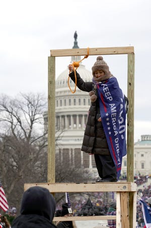 """A person poses with a noose outside the Jan. 6, 2021, """"Stop the Steal"""" rally at the U.S. Capitol building."""