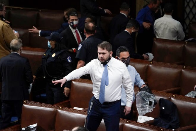 Rep. Ruben Gallego, D-Ariz., stands on a chair as lawmakers prepare to evacuate the floor as mob members try to break into the House Chamber at the U.S. Capitol on Wednesday, Jan. 6, 2021, in Washington.