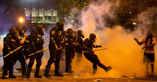 Scenes from a protest in downtown Louisville, Kentucky over the shooting of Breonna Taylor by Louisville police. A police officer kicks a tear gas canister back towards protesters after it was thrown at the police. May 28, 2020